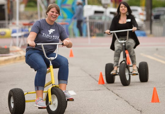 Smokin' Jazz and Barbecue Blues Festival volunteer Lindsey McKenney, left, and Brighton Chamber administrative staffer Kelly Felder ride big trikes sponsored by the Greater Brighton Area Chamber of Commerce at the annual event in downtown Brighton Friday, Sept. 6, 2019.