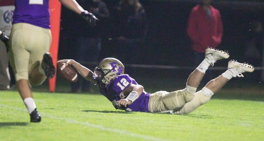 Fowlerville quarterback Kyle Lutz reaches as he slides on his belly just short of the goal line in the game against Corunna Friday, Sept. 6, 2019.
