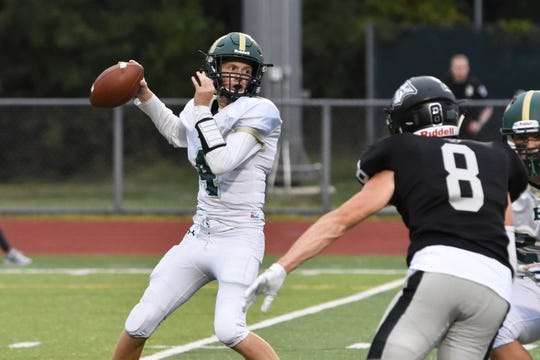 Howell quarterback Zach Metz looks to pass while being pressured by Plymouth's Alec Beshears (8) on Friday, Sept. 6, 2019.
