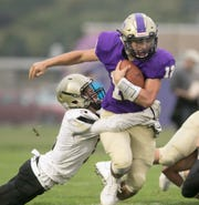 Gladiator quarterback Kyle Lutz carries the ball, dragging Corunna's Ty Anderson with him in the home game Friday, Sept. 6, 2019.