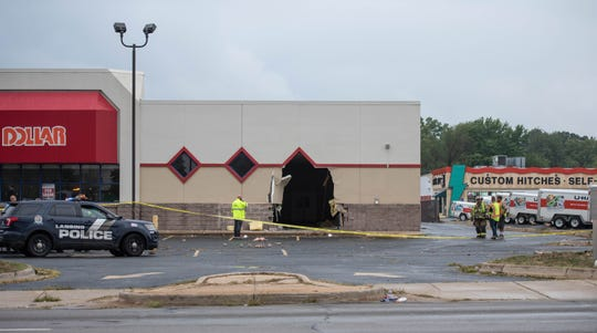 A truck crashed into this vacant Family Dollar at the corner of South Cedar St. and Jolly Road early Friday evening, Sept. 6, 2019. Eyewitnesses said the truck first drove into another building about a block north on Cloverland Drive, then drove backward south on Cedar,  hitting an SUV and then smashing through the Family Dollar. The incident is under investigation.
