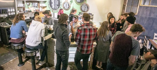 Guests gather in the smaller, intimate location of Blue Owl Coffee in Old Town Lansing.