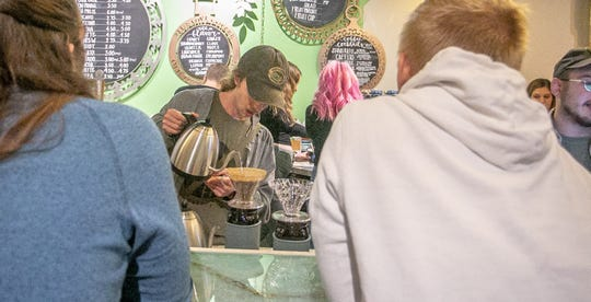 A barista prepares a pour-over coffee in the new Blue Owl Coffee location in Old Town Lansing.