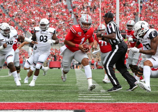 After the pass play broke down, Ohio State quarterback Justin Fields darted up the middle for a 7-yard touchdown, the first of six TDs in a 42-0 win over Cincinnati.