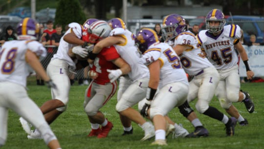 Shelby running back Owen Fisher draws a swarm of Lexington Minutemen on Friday night.