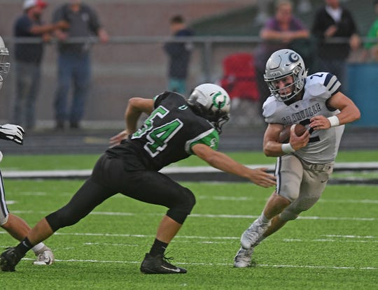 Granville's Bo Buttermore tries to avoid the tackle of the Colt's Brady Au on Friday night at Clear Fork High School.