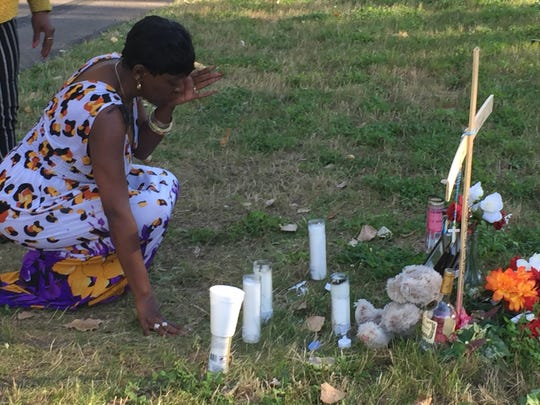 Mary Mathews, the great aunt of Tray Smith, mourns at his shrine during a candlelight vigil Saturday evening.