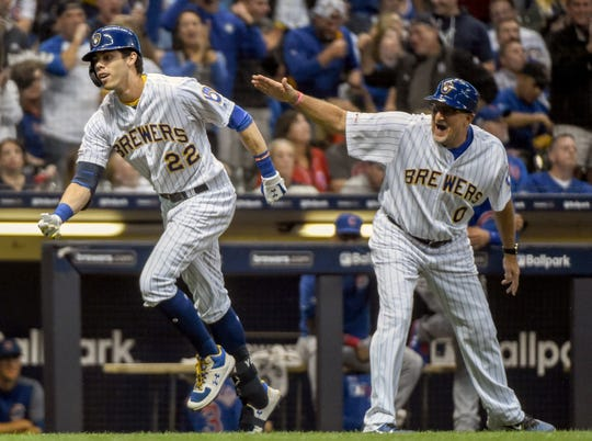 The Brewers' Christian Yelich is greeted by third base coach Ed Sedar after hitting a three-run home run.
