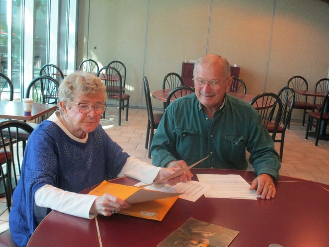 Marilee Goffin, 85, and her half-brother Jim Dostal, 80, go over old photos and documents on Saturday.