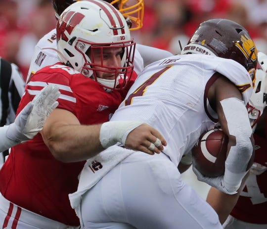 Wisconsin defensive end Garrett Rand tackles Central Michigan running back Kobe Lewis.