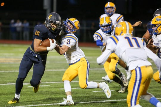 Pequannock's Nick Brizek tries to break away from Butler's Garrett Koppenal during the first half of a football game at Pequannock High School on September 06, 2019.