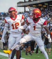 Tuskegee's Peyton Ramzy (1) celebrates scoring the first points of the game against ASU with teammate Steven Hodges (12).
