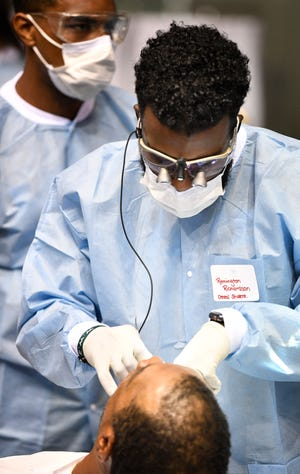 Remington Richardson performs some dental work on a patient during Saint Thomas Health's free health care clinic, Medical Mission at Home, at Municipal Auditorium. The comprehensive clinic provided free medical care including pharmacy services, dental services, mammograms, vision services, foot and wound care, lab services and behavioral medicine. Saturday, Sept. 7, 2019, in Nashville, Tenn.