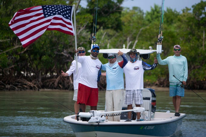 Jaimee Marshall of Painesville, Ohio, waves the flag as he and his team pose for photos during the Take a Soldier Fishing 2019 Tournament, Saturday, Sept. 7, 2019 held at the Hamilton Harbor Yacht Club in Naples.