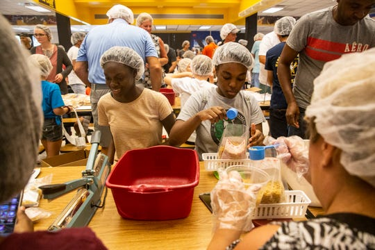 Kisha Petitdo, 16, left, and Janelle Bellot, 17, right, measure macaroni during a meal packing event at Naples High School on Saturday, Sept. 7, 2019. Meals of Hope sponsored this meal packing event to benefit the victims of Hurricane Dorian in the Bahamas.