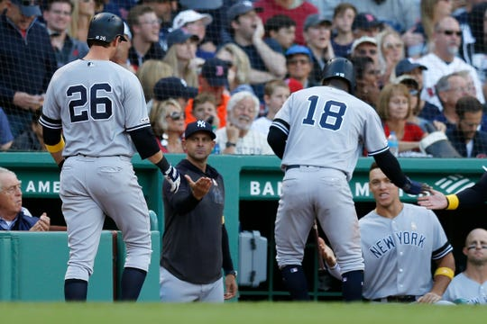 New York Yankees' DJ LeMahieu (26) and Didi Gregorius (18) celebrate after scoring on a ground rule double by Gary Sanchez during the fourth inning of a game against the Boston Red Sox in Boston, Saturday, Sept. 7, 2019.