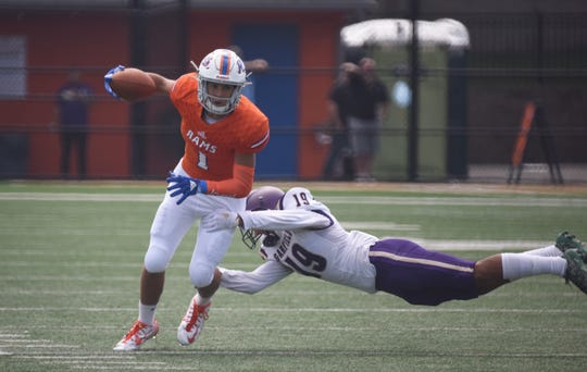 HS football Lodi (orange) vs Garfield (purple)Lodi #1 Aaron Moravick try to avoid a tackle by Garfield # 19 Zachary Cook