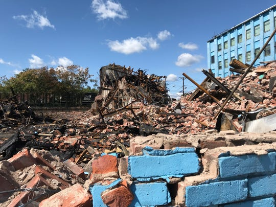 Beyond the distinctive blue wall, a pile of rubble at Straight and Narrow in Paterson.