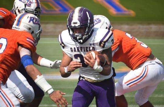 HS football Lodi (orange) vs Garfield (purple)Garfield #32 Josue Matias try to avoid a tackle