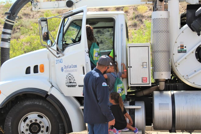 Kids climb into the massive Las Cruces Utilities vactor truck. It's a big vacuum with the primary job of sucking wipes out of clogged city sewer pipes.