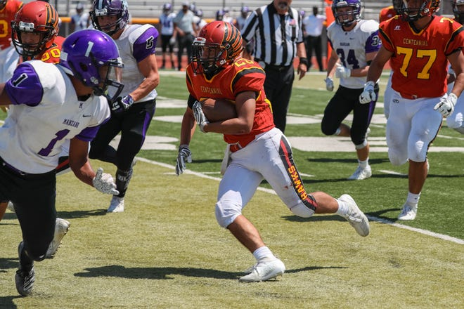 Senior running back Gabriel Acosta (20) runs the ball as the Centennial Hawks face off against the Manzano Monarchs from Albuquerque at the Field of Dreams in Las Cruces on Saturday, Sept. 7, 2019.