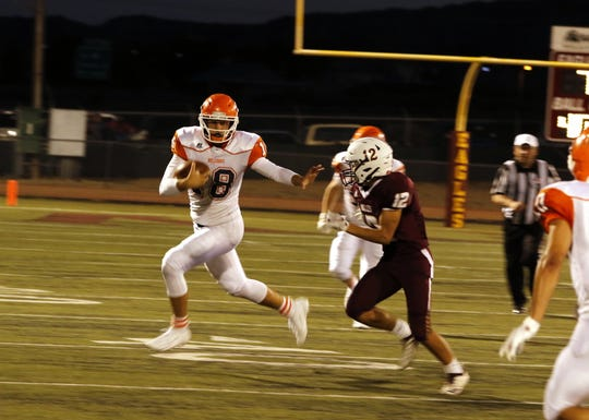 Artesia quarterback Clay Houghtaling prepares to stiff arm a Belen player during their game on Sept. 6, 2019. Houghtaling has almost 2,500 yards of total offense and 35 total touchdowns.