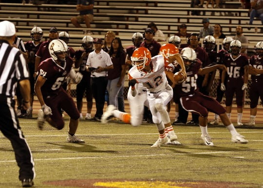 Backup Artesia quarterback Cord Cox scrambles against Belen.