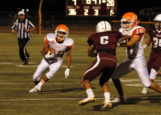 Artesia's Nate Barrera looks for running room against Belen.