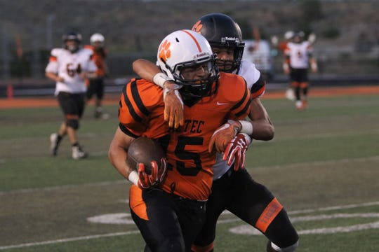 Aztec's Austin Jaime fights for extra yards after making a catch against Taos during Friday's football game at Fred Cook Memorial Stadium in Aztec.