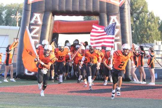 The Aztec Tigers take the field prior to Friday's football game at Fred Cook Memorial Stadium in Aztec.