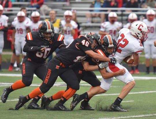 Canton running back Zack Badger runs through several Northville defenders on Friday, September 6, 2019.