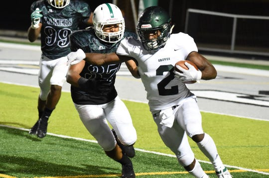 Groves linebacker/running back Ralph Donaldson runs past West Bloomfield defenders in a game on Sept. 6.