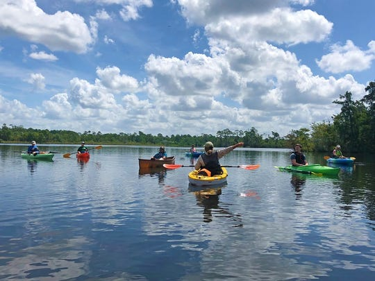At center, Krystal Johnson with Arcadia Mill Archaeological Site points out local flora and fauna on the Blackwater River in a guided kayak tour in July.