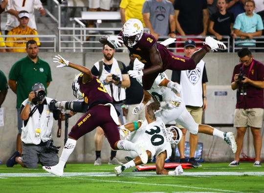 Arizona State Sun Devils wide receiver Brandon Aiyuk (2) dives over Sacramento State Hornets defensive back Allen Perryman (30)  in the first half during a game at Sun Devil Stadium on Sep. 6, 2019 in Tempe, Ariz.