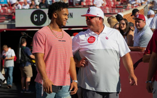 Kyler Murray (left) visits with University of Oklahoma baseball coach Skip Johnson in Murray's return to Norman for the first game of the 2019 season.