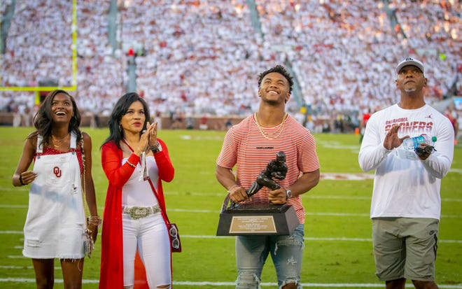 Kyler Murray (second from right) holds up the Heisman Trophy, joined by (from left) his cousin, Carly, his mother, Missy, and his father, Kevin.