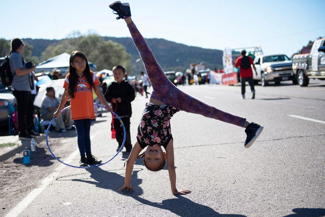 In this Sept. 8, 2018 image, Tomica Johnson, 8, of Fort Defiance, Arizona, does cartwheels during the Navajo Nation Fair Parade near Tse Bonito, New Mexico.