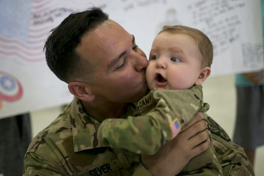 Arizona National Guard Sgt. Anthony Silver (left) kisses his son, 7-month-old Lukas Silver (right), during a deployment ceremony at the Army Aviation Support Facility at Papago Park Military Reservation in Phoenix on Sept. 6, 2019.