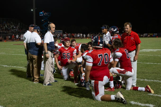 Peoria Centennial football coaches talk to players during the second quarter, September 6, 2019.