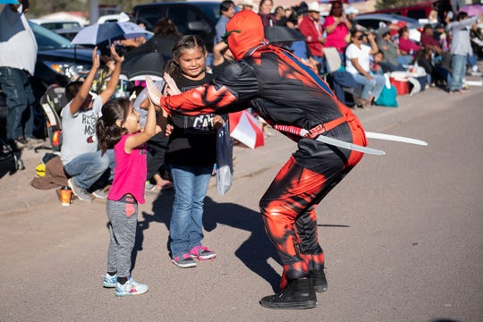 In this Sept. 8, 2018 image, Shania Bruce, 3, gets a high five from a Deadpool character in the Navajo Nation Fair Parade near Tse Bonito, New Mexico.