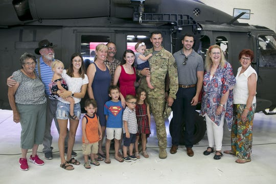 Arizona National Guard Chief Warrant Officer 2 Mario Rossi (center) stands for a photo with his family at a deployment ceremony at the Army Aviation Support Facility at Papago Park Military Reservation in Phoenix on Sept. 6, 2019.