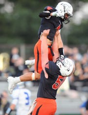 Palmyra's Nick Morder (4) is hoisted into the air by teammate Jacob Miller (50) after scoring his team's first touchdown of the game in the game between the Palmyra H.S. Cougars and the Garden Spot H.S. Spartans played Friday Sept.6,2019 at Palmyra's Buck Swank Stadium.