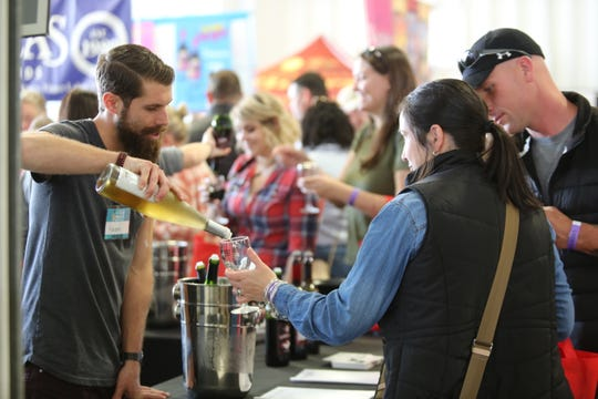Jonathan Lander, tasting room manager at Robibero Family Vineyards in New Paltz, pours a wine sampling for Amanda King of Saylorsburg, Pennsylvania, at the Hudson Valley Wine & Food Fest in Rhinebeck on Sept. 7, 2019.