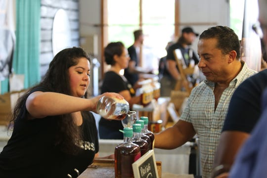 Amber Cannale, with Denning's Point Distillery in Beacon, pours a sample for Carlos Lens of Newburgh at the Hudson Valley Wine & Food Fest in Rhinebeck on Sept. 7, 2019.
