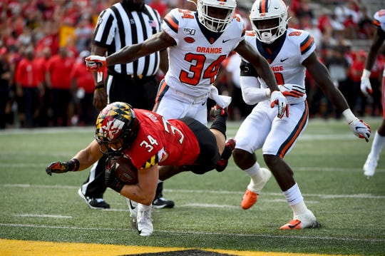 Maryland running back Jake Funk (34) dives for a touchdown in front of Syracuse defensive back Eric Coley (34) during the second half of an NCAA college football game, Saturday, Sept. 7, 2019, in College Park, Md.