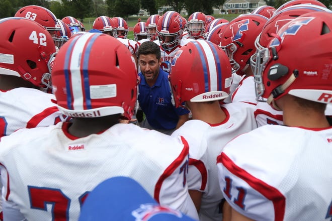 Fairport head coach Marc Vitticore talks to his team in the huddle before the start of the game.