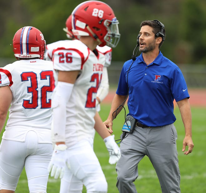 Fairport's head coach Marc Vitticore talks to his team as they come over during a timeout.
