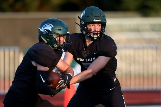 West Salem's Jackson Lowery (5) hands the ball off to Jacob Tinseth (2) in the Lake Oswego vs. West Salem football game at West Salem High School on Sep. 6, 2019. Lake Oswego won the game 42-21.