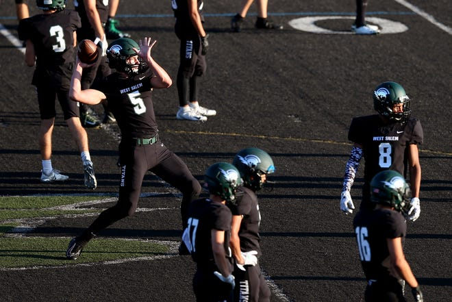 West Salem's Jackson Lowery (5) and others warm up before the start of the Lake Oswego vs. West Salem football game at West Salem High School on Sep. 6, 2019. Lake Oswego won the game 42-21.