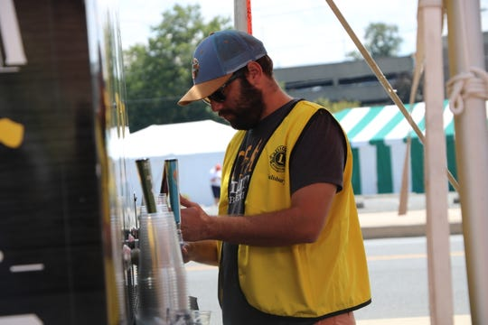 Volunteers from the Salisbury Lions Club pour Evolution beer at the National Folk Festival Saturday, Sept. 7, 2019 in Salisbury.